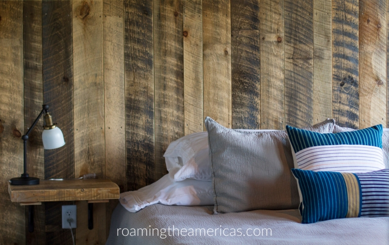 Bed with pillows and a wood-paneled wall at the Mill Inn + Cafe in Dover, Maine