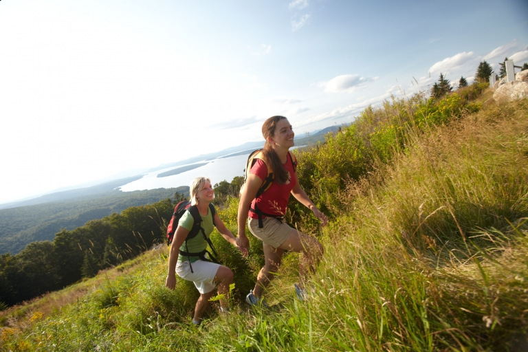 Two women hiking up a mountain overlooking a lake in western Maine