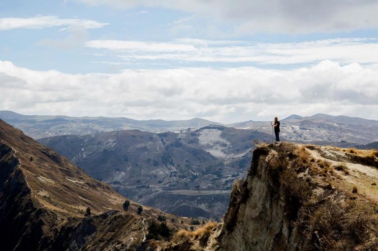 Woman standing on a cliff near Lake Quilotoa in Ecuador