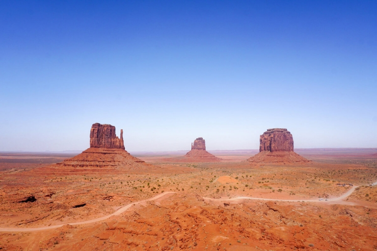 Red sandstone buttes and mesas with a road and bright blue sky in Monument Valley Tribal Park