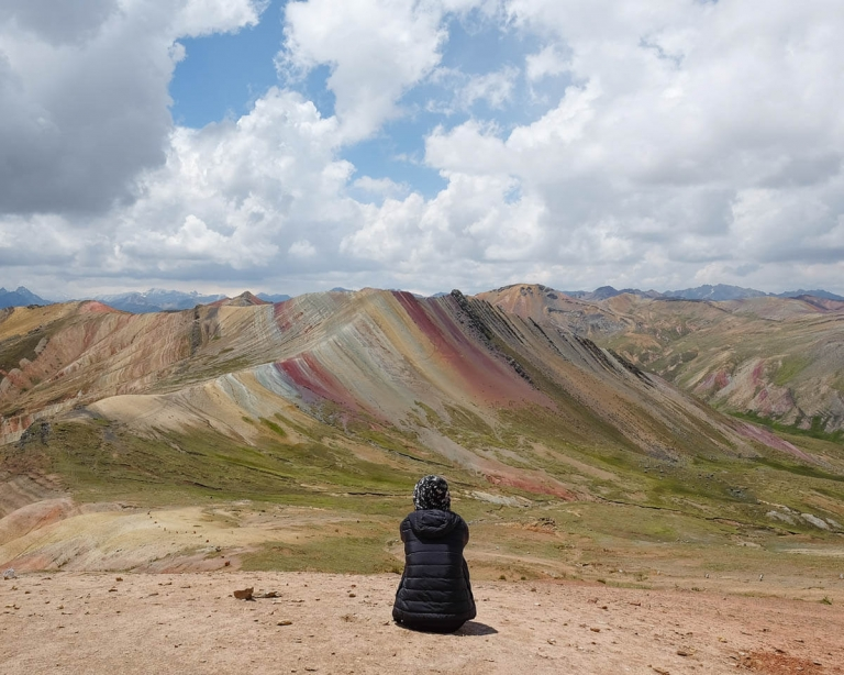 Girl sitting at Palccoyo Rainbow Mountain in Peru