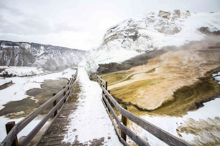 Boardwalk in Yellowstone National Park covered with snow in the winter with mountains in the background