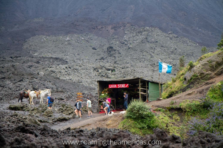 People and horses in front of the Lava Store in the crater of Pacaya Volcano in Guatemala