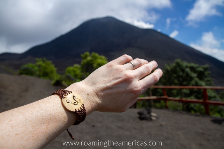 Woman wearing a bracelet with the Guatemalan national bird on it, in front of Pacaya Volcano