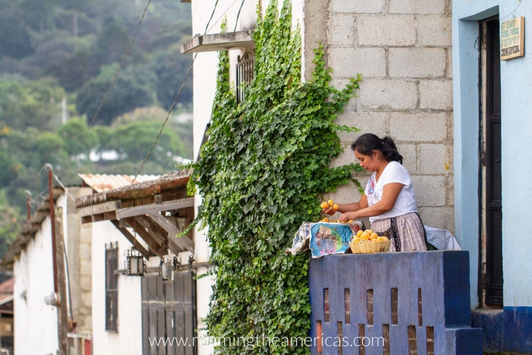 A woman in a small town near Antigua, Guatemala standing on her porch sorting fruit
