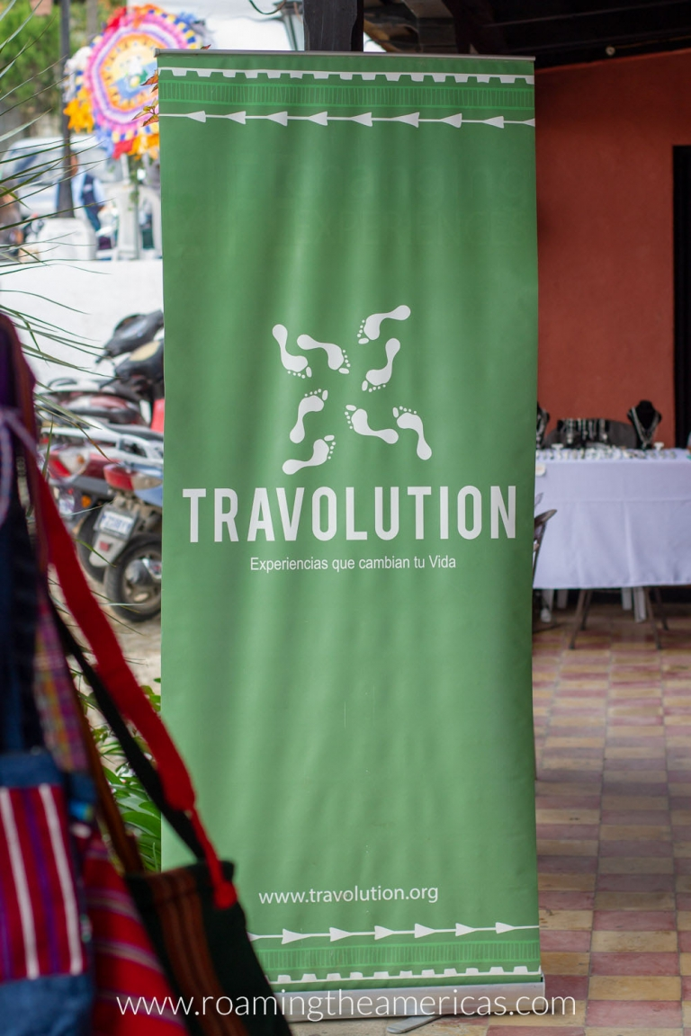"Green sign that says ""Travolution"" at the Central American Community Tourism Conference in San Cristobal El Alto, Guatemala"