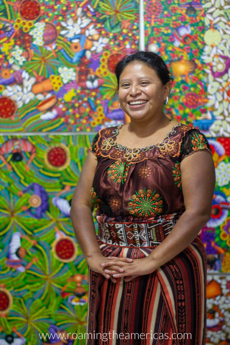 Woman standing in front of paintings at an artist cooperative in San Juan La Laguna on Lake Atitlan, Guatemala