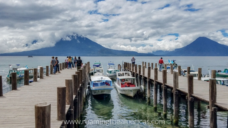 Boats at the docks at Santa Catarina Palopó on Lake Atitlan with volcanoes in the background