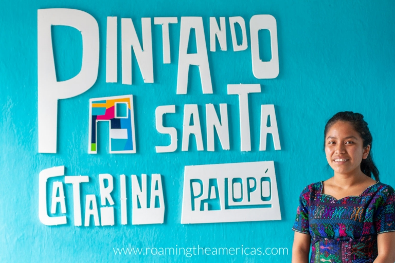 "Young woman in front of sign that says ""Pintando Santa Catarina Palopó"""