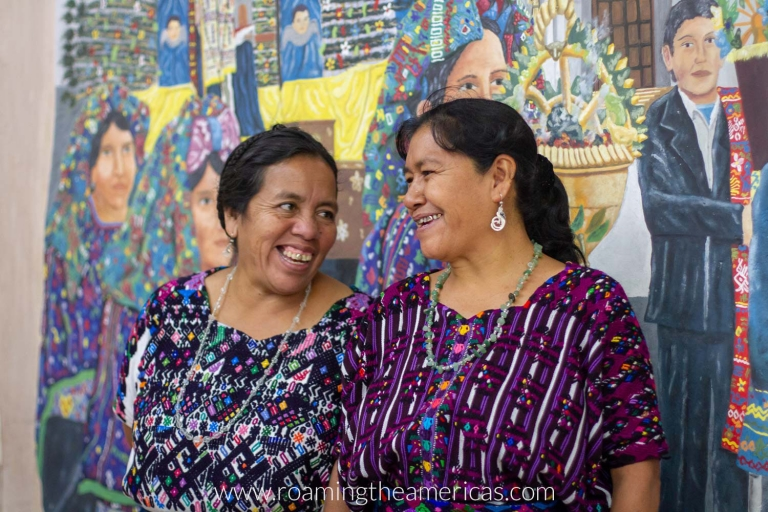 Two Mayan women standing in front of a mural in the town hall of Santo Domingo Xenacoj, Guatemala
