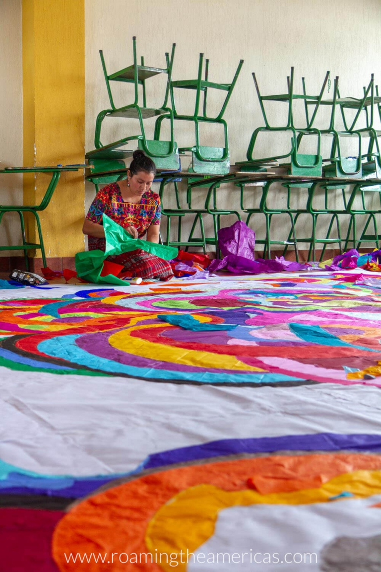 A Guatemalan woman cutting out tissue paper in a classroom with a giant colorful kite in front of her