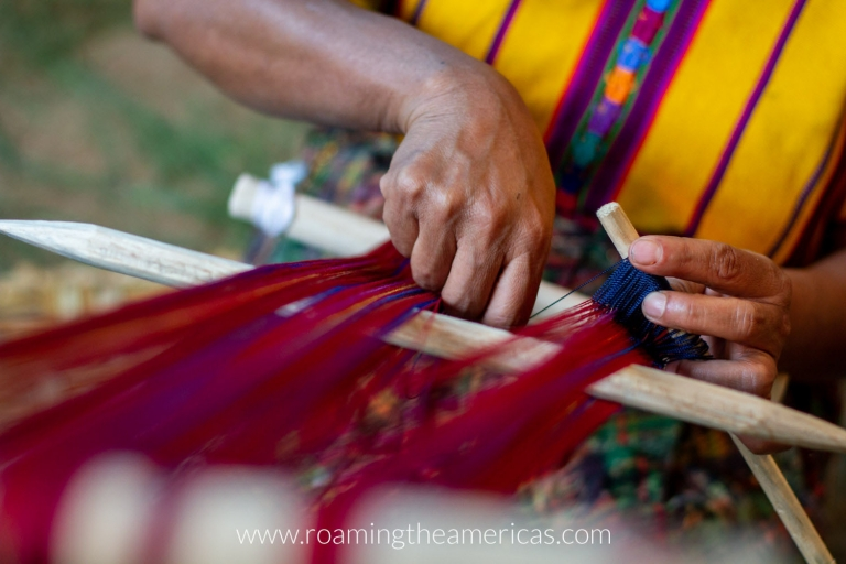 Woman weaving red and blue designs by hand in Santo Domingo Xenacoj, Guatemala