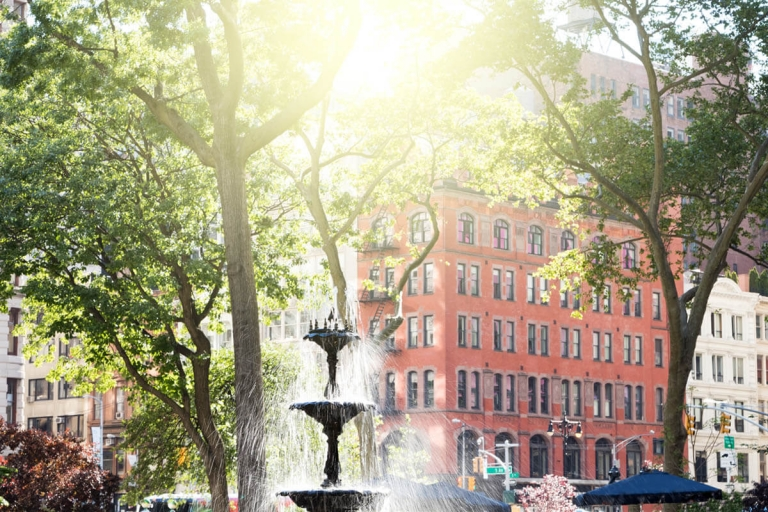 Fountain in Madison Square Park with sunlight shining through it and New York City buildings in the background