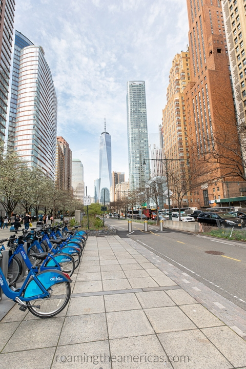 Citibike station in New York City on a bike path with the World Trade Center in the background