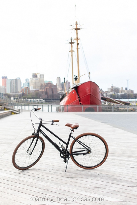 Bike on a dock in NYC overlooking the river with a red ship in the background