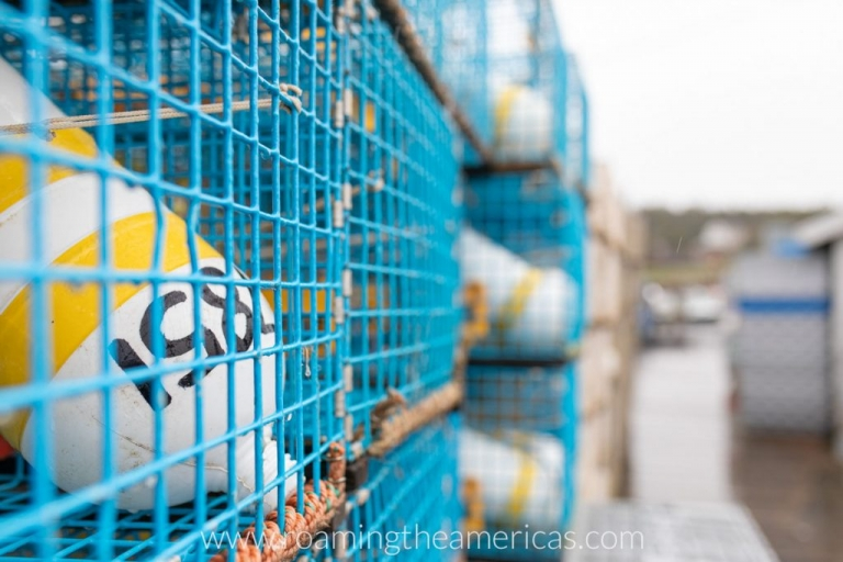 Yellow and white lobster buoys inside bright blue traps on a dock on Deer Isle, Maine