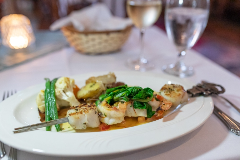 Grilled shrimp and scallops topped with local greens and a side of vegetables on a table at Arborvine