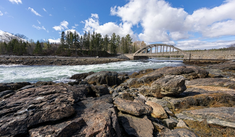 Reversing falls going under a bridge and rocky shores in Blue Hill, Maine