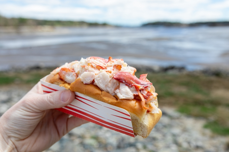 Woman holding a lobster roll in front of the ocean in Blue Hill, Maine