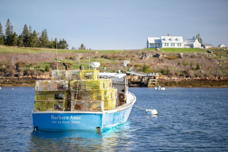 "Lobster boat named ""Barbara Anne"" with a pile of lobster traps and a house on top of a hill in the distance in the harbor at Isle au Haut, Maine"