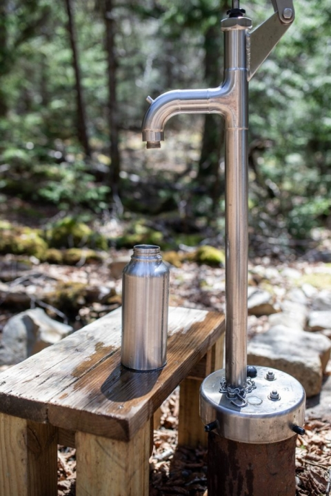 Refillable stainless steel water bottle on a bench by the water pump