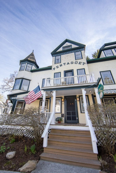 Front of the historic Pentagoet Inn with an American flag waving in the wind in Castine, Maine