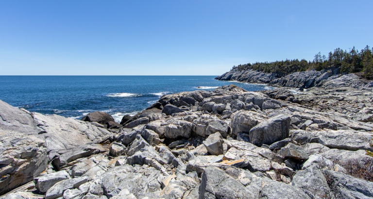 Rocky cliffs overlooking Atlantic ocean on a sunny day on Isle au Haut, Maine