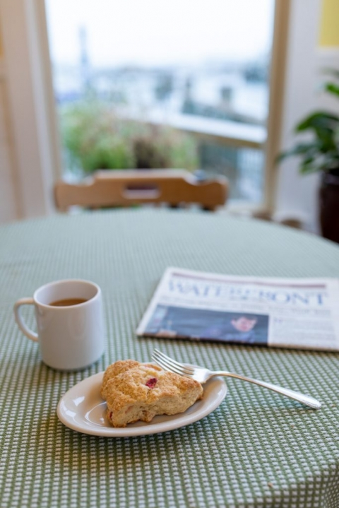 Berry scone on a plate with a fork, coffee, and a local newspaper on a green and white checkered tablecloth in front of a window that overlooks Stonington Harbor