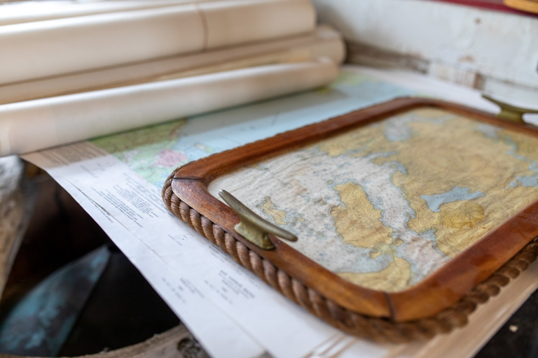 A map serving tray on top of maritime maps inside a shop in Stonington, Maine