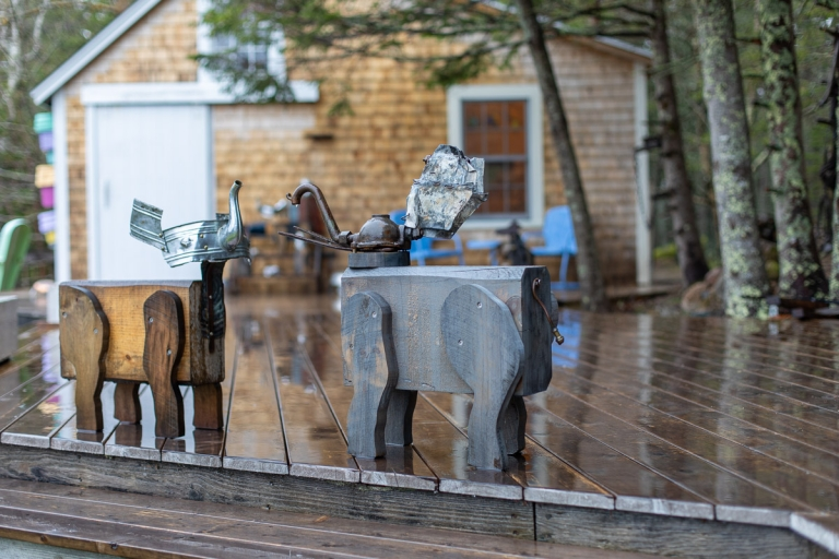 Two animal art figures made of wood and metal on a porch at Nervous Nellie's on Deer Isle