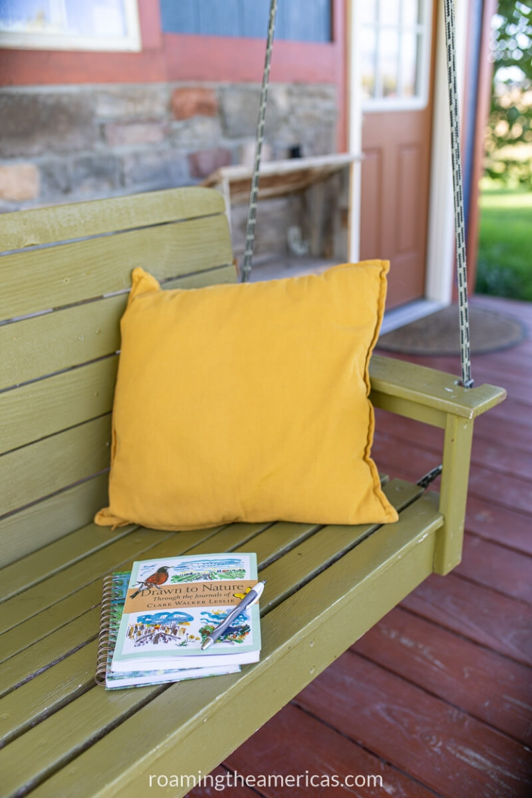 Journal and book on a porch swing with a yellow pillow