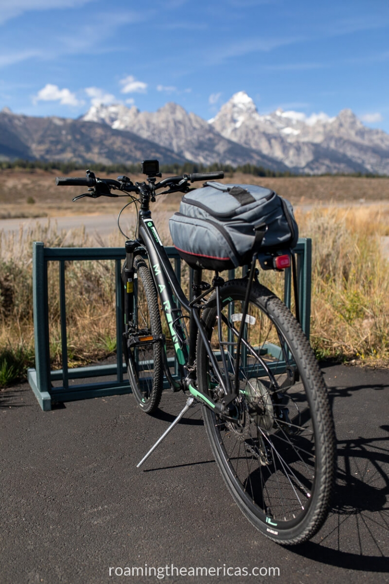 Bike parked near the entrance of Grand Teton National Park with the mountains in the background.