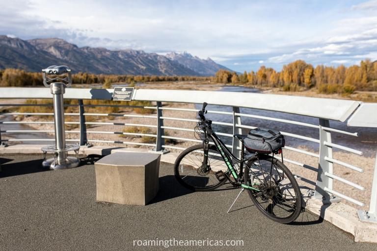 Bike and viewfinder binoculars on the Pathway Bridge overlooking the Snake River and mountains in the background.